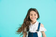 Haircare, hairstyle, hairdresser, barber. Girl smile with flowing long wavy hair on blue background. Child smiling with healthy brunette hair. Kid beauty salon Royalty Free Stock Images
