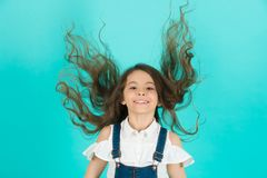 Haircare, hairstyle, hairdresser, barber. Girl smile with flying hair on blue background. Child smiling with long healthy hair. Beauty salon concept, punchy Royalty Free Stock Images
