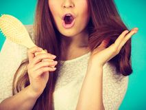 Shocked amazed woman holding hair brush. Haircare and morning hairstyling concept. Shocked amazed with wide open mouth woman holding hair brush Stock Photos
