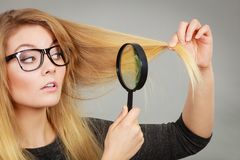 Woman holding magnifying glass looking at hair Stock Images