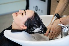 Haircare procedure in beauty salon. Hairdresser is brushing woman`s hair spreading a treatment mask or conditioner
