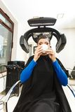 Woman in hairdresser drinking coffee under machine Royalty Free Stock Images