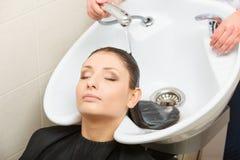 Hairdresser washing her woman customer hair Royalty Free Stock Image