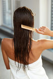 Haircare. Woman Brushing Beautiful Long Healthy Hair With Comb Stock Photo