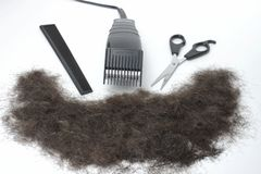 Haircut. Electric hair clippers, scissors, and a barber's comb arranged on a white background in front of a pile of hair stock images