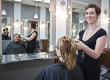 Haircut. Women getting a haircut at a beauty salon royalty free stock photo