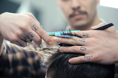 Haircut at barber shop. Barbershop. Closeup of barbers tattooed hands combing hair making haircut to a male client Stock Image