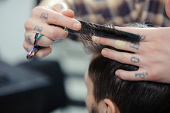 Haircut at barber shop. Barbershop. Closeup of barbers tattooed hands combing hair making haircut to a male client Stock Images