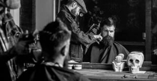 Haircut concept. Barber with hair clipper works on hairstyle for man with beard, barbershop background. Hipster client. Haircut concept. Barber with hair clipper royalty free stock images