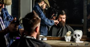 Haircut concept. Barber with hair clipper works on hairstyle for man with beard, barbershop background. Hipster client. Haircut concept. Barber with hair clipper royalty free stock photos