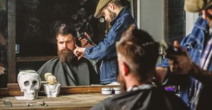Haircut concept. Barber with hair clipper works on hairstyle for man with beard, barbershop background. Hipster client royalty free stock photo