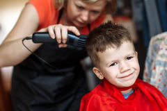 Haircut for little boy at barber Stock Images