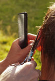Haircut scissors. Female hand holding scissors and a comb during a haircut, close-up, outdoors Stock Photography