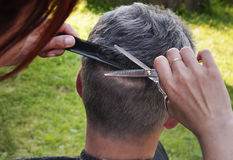Haircut scissors. Female hand holding scissors and a comb during a haircut, close-up, outdoors Stock Photo