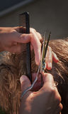 Haircut scissors. Female hand holding scissors and a comb during a haircut, close-up, outdoors Royalty Free Stock Images