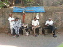 Haircut  sir !!. Men waiting for there haircut on the street of mumbai Stock Photos