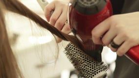 Haircutter χρησιμοποιώντας το στεγνωτήρα για την ξήρανση της θηλυκών τρίχας και της βούρτσας γηα τα μαλλιά για τον προσδιορισμό μ φιλμ μικρού μήκους