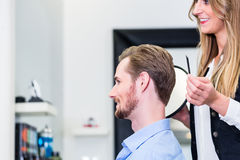 Haircutter showing customer his new cut Stock Image