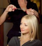 Haircutter snitthår i salong. Blond kvinna Royaltyfri Fotografi