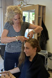 At the hairdersser. Young girl with long blond hair at the hairdresser, she gets a new hairstyle, braided hair round the head Stock Photography