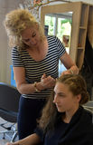 At the hairdersser. Young girl with long blond hair at the hairdresser, she gets a new hairstyle, braided hair round the head Royalty Free Stock Images