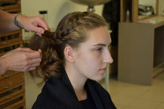 At the hairdersser. Young girl with long blond hair at the hairdresser, she gets a new hairstyle, braided hair round the head Stock Images