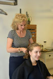 At the hairdersser. Young girl with long blond hair at the hairdresser, she gets a new hairstyle, braided hair round the head Stock Photos