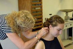 At the hairdersser. Young girl with long blond hair at the hairdresser, she gets a new hairstyle, braided hair round the head Royalty Free Stock Photos
