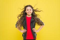 Hairdo для ее формы стороны Счастливая девушка наслаждаясь ее новым hairdo на желтой предпосылке Немногое ребенок с милой улыбкой стоковое фото rf