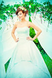 Hairdo. Beautiful bride with chaming red hair stands under the wedding arch. Wedding dress and accessories. Wedding decoration Stock Photo