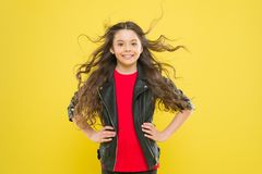 Hairdo for her face shape. Happy girl enjoying her new hairdo on yellow background. Little child with cute smile and royalty free stock photo