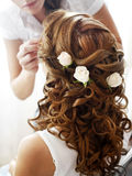 Hairdress of the bride. Decorated with flowers Stock Photo