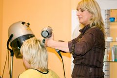 At the hairdresser. Blond hairdresser with her client, removing the covering material Royalty Free Stock Photos