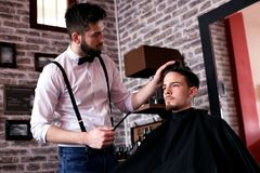 Hairdresser adjusts hair a customer with a comb royalty free stock image