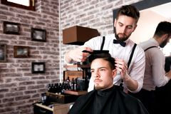 Hairdresser adjusts hair a customer with a comb royalty free stock photo