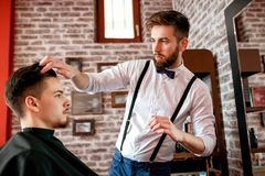 Hairdresser adjusts hair a customer with a gel Royalty Free Stock Image
