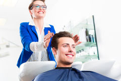 Hairdresser advice man on haircut in barbershop Stock Image