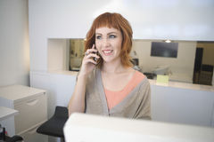 Hairdresser Answering Mobilephone At Reception In Salon. Beautiful young hairdresser answering mobilephone at reception in salon Royalty Free Stock Image