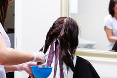 Hairdresser applying color female customer at salon, doing hair dye Royalty Free Stock Images