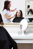 Hairdresser applying color female customer at salon, doing hair dye Royalty Free Stock Photography