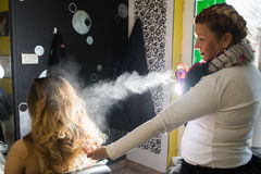 Hairdresser applying hair spray on ombre hair Royalty Free Stock Images