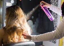 Hairdresser applying hair spray on ombre hair Stock Photos