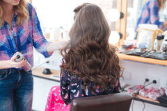Hairdresser applying hairspray for long curly hair of woman Royalty Free Stock Photo