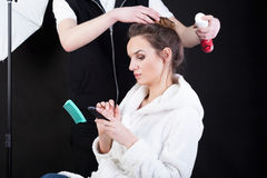 Hairdresser applying spray on model's hair Stock Photo