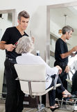 Hairdresser Attending Woman At Salon Stock Photo