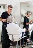 Hairdresser Attending Woman At Salon Stock Photo