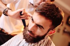 Hairdresser or barber does a hairstyle to the client royalty free stock photo