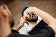 Hairdresser in barber shop cutting beard with razor. View from above of young brunet men visiting barber shop, and hairdresser caring about face, cutting beard royalty free stock photos