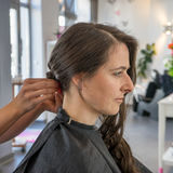 At the hairdresser. A beautiful woman is able to hair her hair Royalty Free Stock Photo
