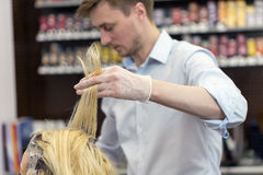 A hairdresser bleaching hair for a blonde female Stock Images